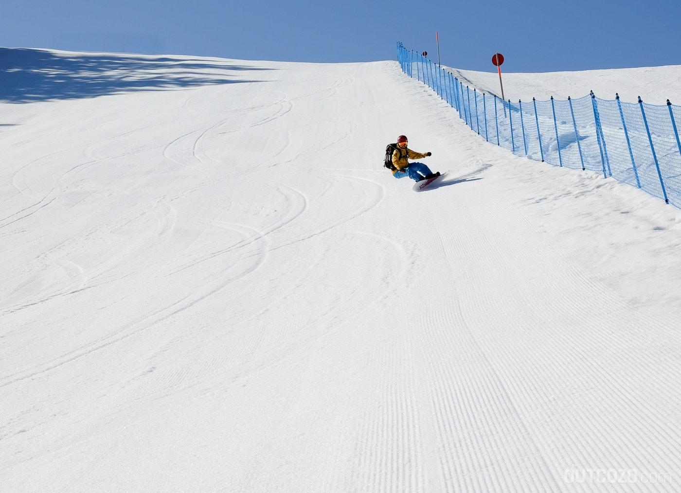 Carven mit Snowboard auf leerer Piste